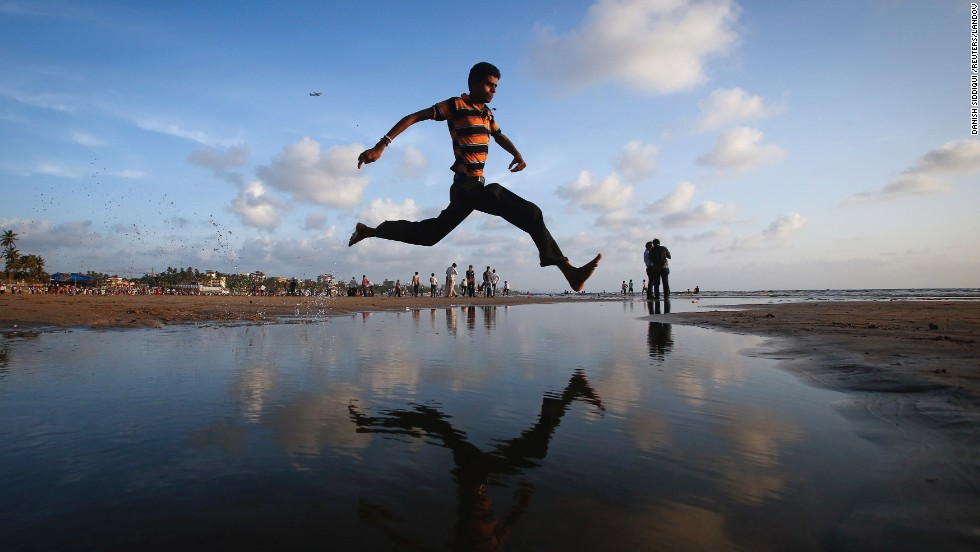 "A man jumps over a water stream on a beach along the Arabian Sea in Mumbai, India, on September 2. <a href=""http://www.cnn.com/2013/08/28/world/gallery/week-in-weather-0828/index.html"">View last week's best weather photos.</a>"