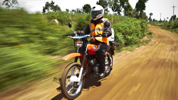 Joel Otieno, a clinical health assistant at the FACES community-based organization in Kenya, rides to his next appointment. He is supported by an organization called Riders for Health, founded by Andrea and Barry Coleman, who share a passion for motorcycles. Through the racing world, they became involved in fundraising for children in Africa and soon recognized the vital role of transportation in providing health care.