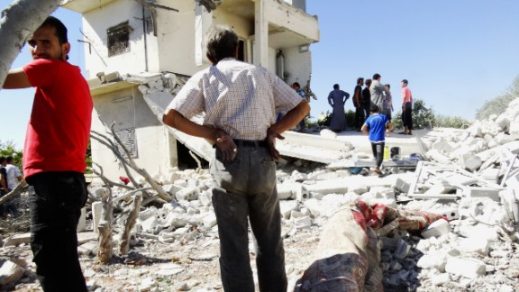 Men gather on the remains of a destroyed building after reported airstrikes by Syrian government forces in the rebel-held northwestern Syrian province of Idlib on Thursday, September 5.