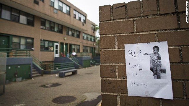 A memorial to Antiq Hennis is posted on a wall outside an apartment complex in the Brownsville neighborhood in Brooklyn.