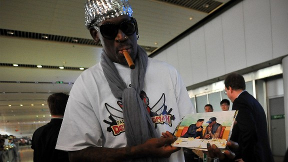 Former US basketball player Dennis Rodman shows pictures of him reportedly with North Korean leader Kim Jong-Un to media as he arrives at Beijing International Airport on September 7, 2013. Rodman returned to China from Pyongyang on September 7 after a five-day trip when he met Kim Jong-Un, but without jailed American Kenneth Bae.