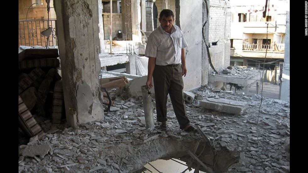 A man stands inside a home damaged by heavy shelling in Arbeen, a suburb of Damascus, Syria, on September 7.