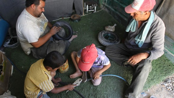 Syrian refugee workers fix cart wheels at their shop at the Zaatari refugee camp in September 2013.
