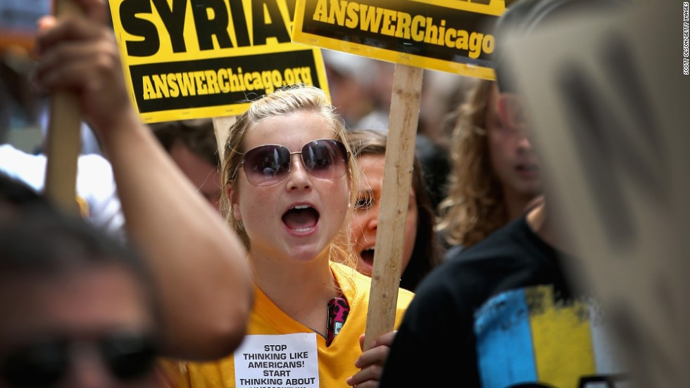 People carry signs to protest U.S. intervention in Syria on September 7 in Chicago.