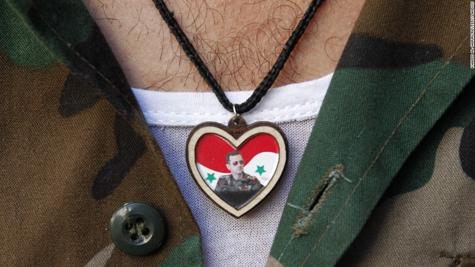 A soldier wears a picture of Syrian President Bashar al-Assad on his chest while at a market in old Damascus on September 8.