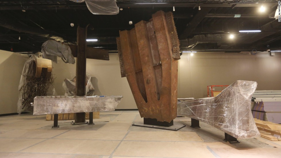 "The ""Cross,"" made of intersecting steel beams found in the rubble of 6 World Trade Center, and a fragment of a trident column, center, one of 84 that formed the exterior structure of each tower, are prepared for display."