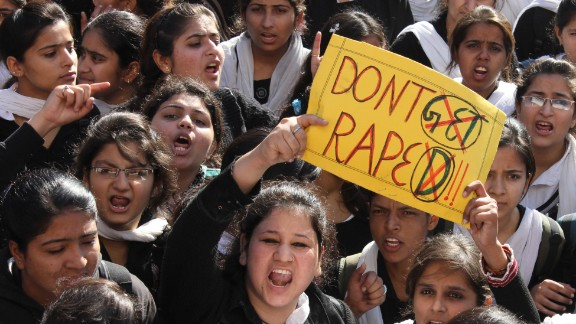 Protesters hold signs in outrage over the gang-rape and death of a 23-year-old student in Delhi in 2012.
