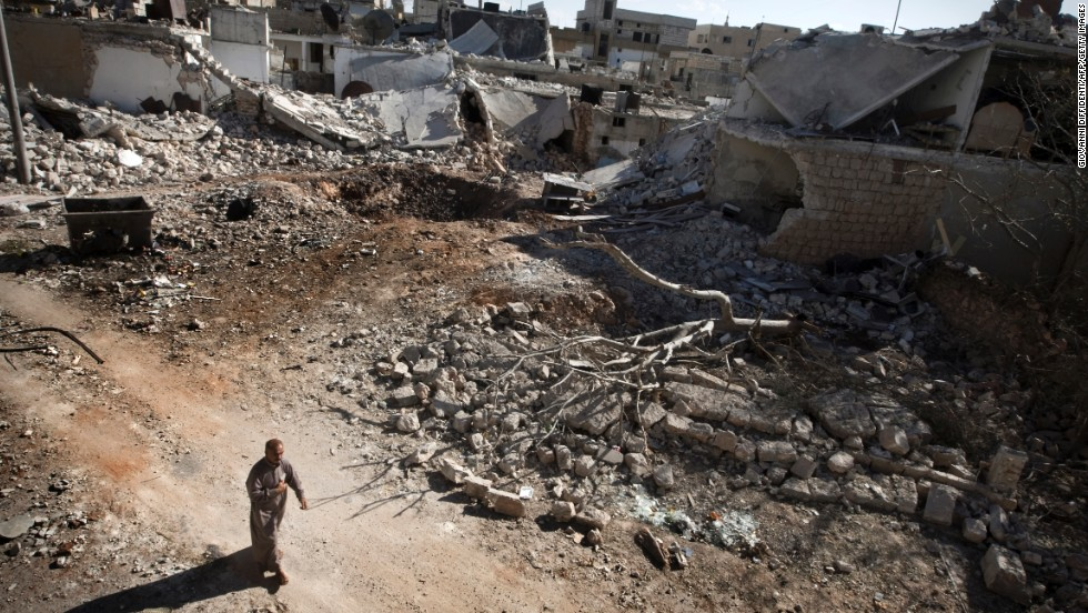 A man walks through a destroyed residential area of Saraqib, Syria, on Monday, September 9, following repeated airstrikes by government forces.