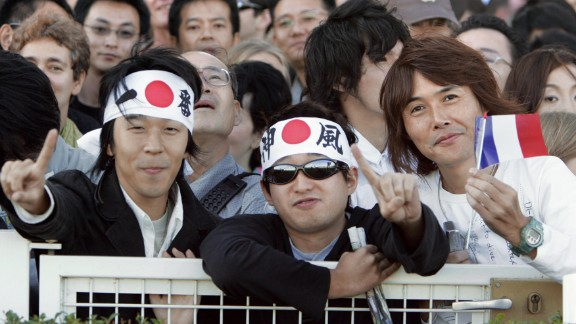 Japanese support the horse, Deep Impact and his jockey Yutake Take of Japan which attract a huge fan club, during the Prix de l'Arc de Triomphe's race at Longchamp, 01 October 2005 in Paris. Around 5,000 Japanese nationals had travelled over to Longchamp, in western Paris to see the five-year-old colt take on Europe's finest including last year's champion Hurricane Run but that did not deter them from queuing up at a specially designated betting stall solely for Japanese punters. AFP PHOTO BERTRAND GUAY (Photo credit should read BERTRAND GUAY/AFP/Getty Images)