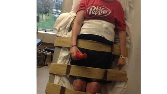 """Emily stands on the tilt table at the rehab hospital on February 22. """"Emily has achieved some great things this week,"""" wrote her mother in a daily Facebook update. The teenager was finally able to use her right hand and she faced the tilt table without """"any pain, dizziness, or tears."""""""