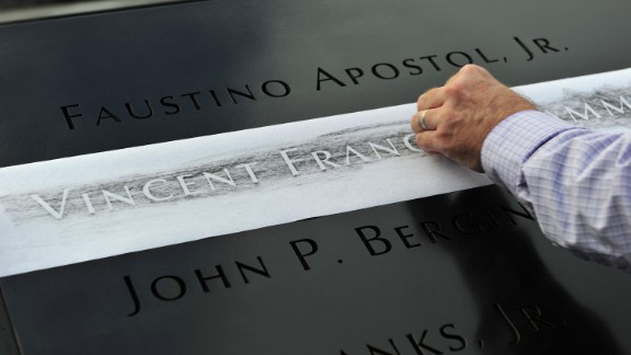 A man makes a rubbing of his friend's name, New York firefighter Vincent Giammona, at the south pool of the 9/11 Memorial on September 11.