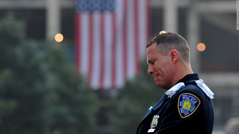 Daniel Henry, a police officer with the Port Authority of New York and New Jersey, pauses during a moment of silence at the south reflecting pool of the 9/11 Memorial in New York on September 11.