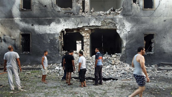 People gather outside the building that was hit by a car bomb.