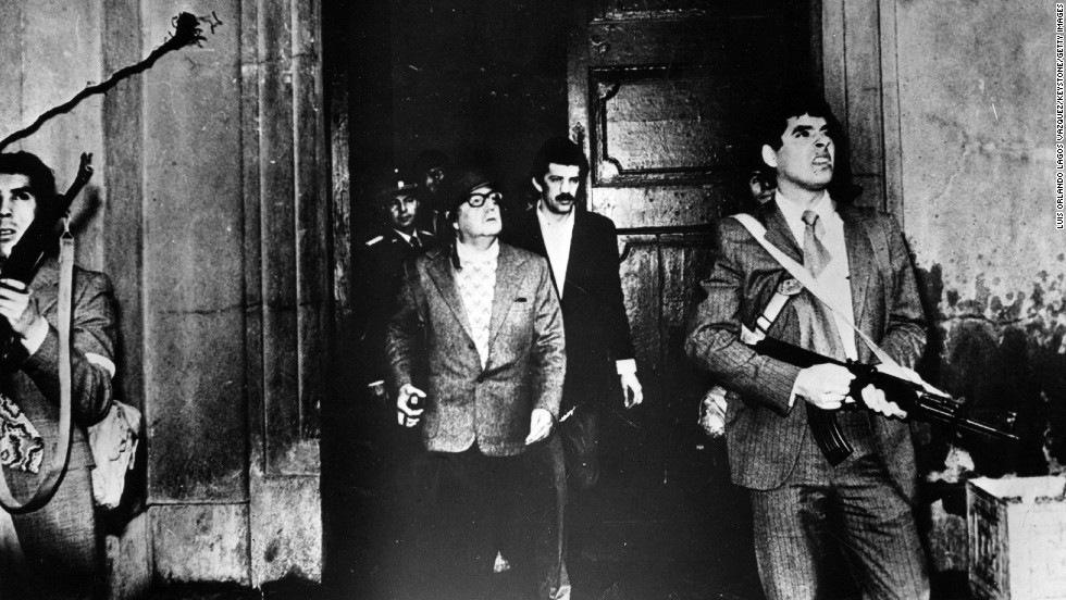 Armed guards watch out for attackers as Allende leaves the Moneda Presidential Palace during the military coup in which he was overthrown and killed in the palace on September 11, 1973. This is said to be the last photo of the president.