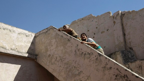 Free Syrian Army fighters climb a flight of stairs to take positions near the Hanano barracks on September 11.