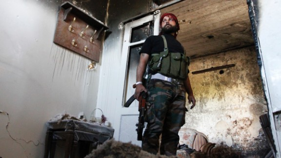 A Free Syrian Army fighter stands guard inside a damaged house in Aleppo
