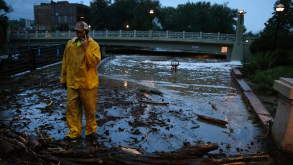 A city worker talks on his phone while surveying high water levels from Boulder Creek after flash flooding in downtown Boulder, Colorado, on September 12.