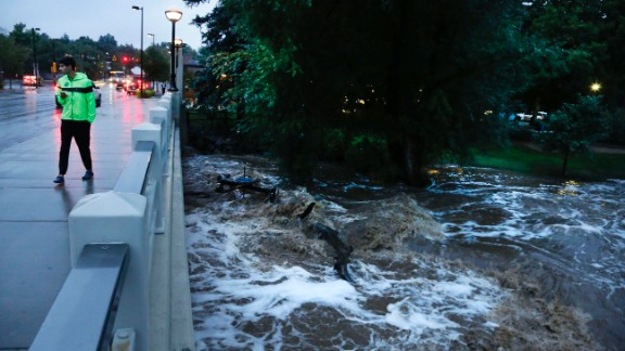 A man walks past the swelled Boulder Creek in Boulder on September 12.