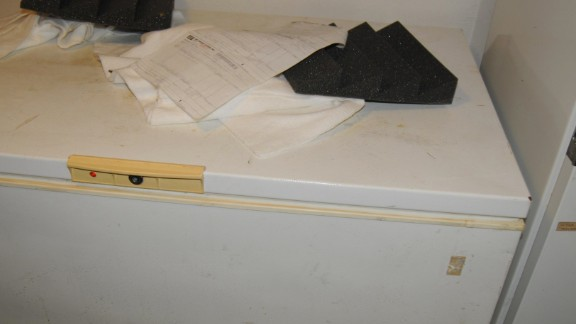 A freezer next to the door to the soundproof room. Sitting on top are pieces of black foam to make the room soundproof.