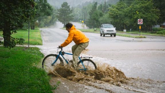 Joey Schusler rides through flooded Canyon Boulevard in Boulder, on September 12.