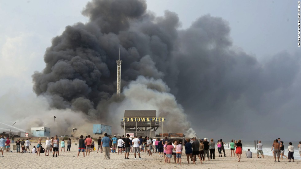 Onlookers line the beach as smoke rises from the boardwalk.