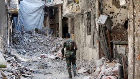 A sheet hangs across an alley way to shield fighters from sniper fire as a fighter of the Popular Front for the Liberation of Palestine General Command walks past destroyed buildings in the Yarmouk refugee camp in Damascus, Syria, on September 12.