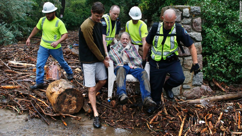 Will Pitner gets rescued by emergency workers and neighbor Jeff Writer on September 13 after he spent a night trapped outside above his home at the base of Boulder Canyon.