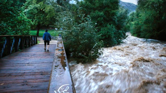 During a break in the rain, a woman walks over a footbridge past the raging Boulder Creek in Boulder on September 13. Boulder County is one of the hardest-hit areas.