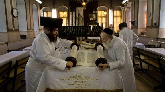 Ultra-Orthodox Jewish men roll a Torah scroll ahead of Yom Kippur in Jerusalem.