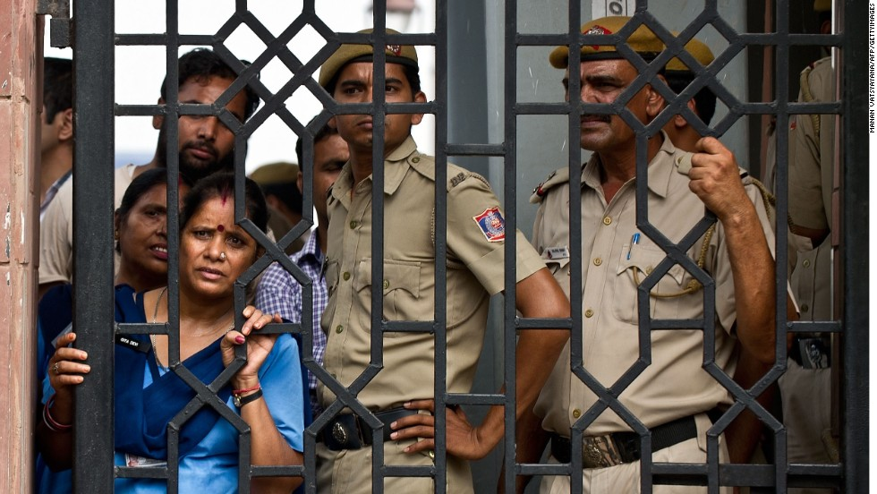 Indian court staff and police officers watch demonstrators shout slogans after the sentencing at the Saket courthouse in New Delhi.