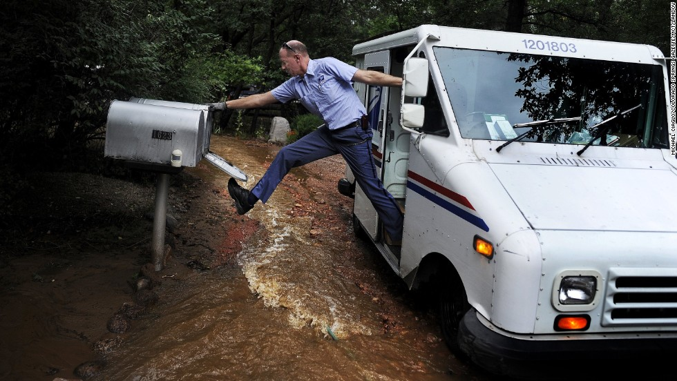 Dave Jackson closes a mailbox with his foot after delivering the mail to a home surrounded by water from the flooded Cheyenne Creek in Colorado Springs, Colorado, on Friday, September 13.