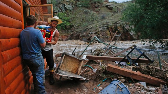 Chris Rodes helps Fred Rob salvage a friend's belongings after floods left homes in a shambles in Lyons, Colorado.