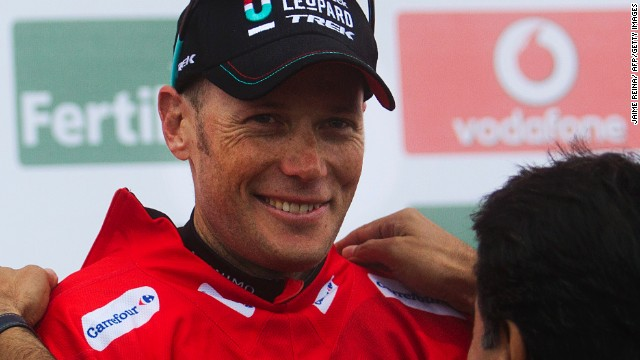 Chris Horner dons the race leader's red jersey on his way to winning the Tour of Spain cycling race.