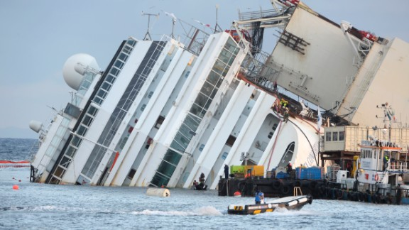 Members of the US salvage company Titan and Italian firm Micoperi work at the wreck of Italy's Costa Concordia cruise ship near the harbour of Giglio Porto on September 16, 2013. Salvage workers will attempt to raise the cruise ship today, in the largest and most expensive maritime salvage operation in history, so-called 'parbuckling', to rotated the ship by a series of cables and hydraulic machines. Thirty-two people died when the ship, with 4,200 passengers onboard, hit rocks and ran aground off the island of Giglio on January 2012. AFP PHOTO / ANDREAS SOLARO (Photo credit should read ANDREAS SOLARO/AFP/Getty Images)