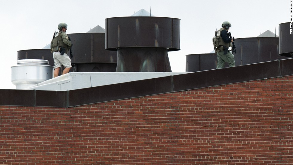 Police officers walk on a rooftop at the Washington Navy Yard.