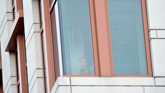 A woman watches from an office building as police respond to the shooting.
