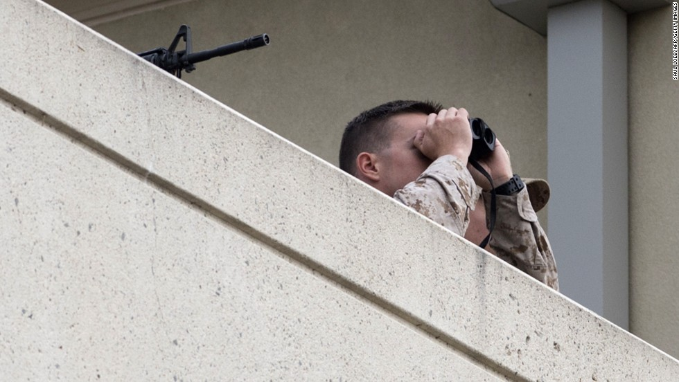 Military security observes the scene from a nearby rooftop.