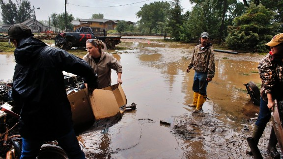 Local residents, from left, Levi Wolfe, Miranda Woodard, Tyler Sadar, and Genevieve Marquez help salvage and clean property after days of flooding in Hygeine, Colorado, on September 16.