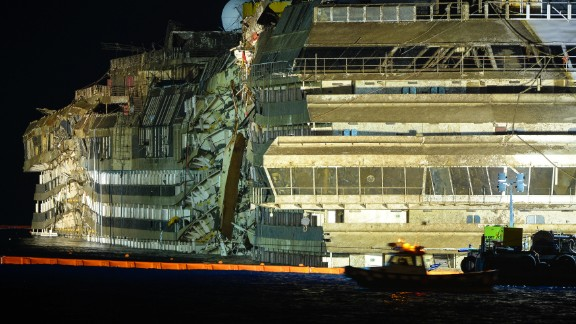 The wreck of Italy's Costa Concordia cruise ship begins to emerge from water on September 17, 2013 near the harbour of Giglio Porto. Salvage workers attempt to raise the cruise ship today and tonight, in the largest and most expensive maritime salvage operation in history, so-called 'parbuckling', rotating the ship by a series of cables and hydraulic machines. Thirty-two people died when the ship, with 4,200 passengers onboard, hit rocks and ran aground off the island of Giglio on January 2012. AFP PHOTO / ANDREAS SOLARO (Photo credit should read ANDREAS SOLARO/AFP/Getty Images)