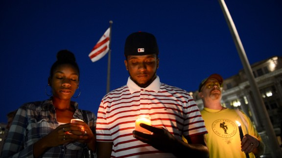 From left, Brittany Carter, Jibri Johnson and Bryan Beard attend a small candlelight vigil at Freedom Plaza in Washington on September 16.