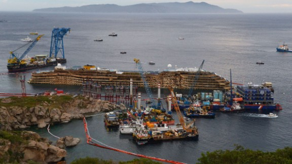 """The wreckage of the Costa Concordia cruise ship sits near the harbor of Giglio on Tuesday, September 17, after a <a href=""""https://www.cnn.com/2013/07/18/europe/gallery/costa-concordia/www.cnn.com/2013/09/15/world/europe/italy-costa-concordia-salvage/index.html"""" target=""""_blank"""">salvage crew rolled the ship off its side</a>."""