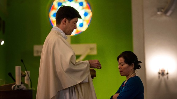 The Rev. Andrew Royals offers communion to Vinh Tran during a Catholic Mass at the St. Vincent De Paul Church on September 16. A prayer for the shooting victims was held at the church, which is just blocks away from the site of the violence.