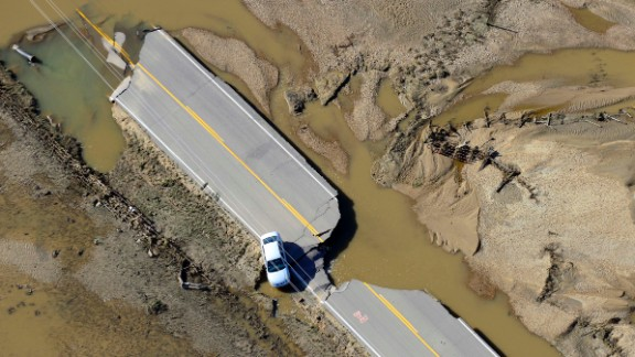An abandoned car sits on a destroyed road along the South Platte River near Greeley, Colorado, on Tuesday, September 17.