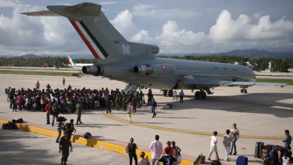 Stranded tourists gather around a Mexican air force plane at the air base in Pie de la Cuesta, near Acapulco, as they wait to be evacuated on September 17. An estimated 40,000 tourists were stranded in the Pacific state of Guerrero as dozens of roads were damaged and Acapulco