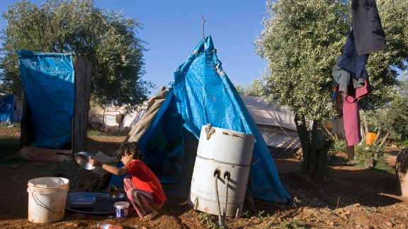 A young Syrian girl washes a pan at the Atme refugee camp along the Turkish border in September 2013.