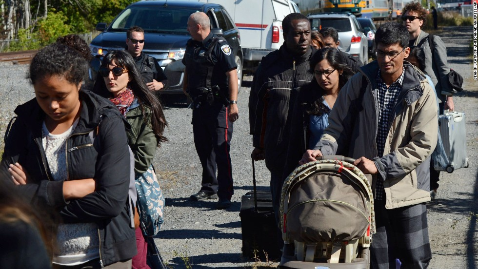 Train passengers are escorted away from the crash site on September 18.
