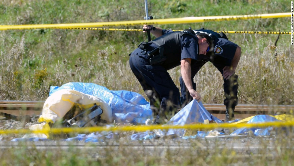 Police officers look under a tarp at the scene on September 18.