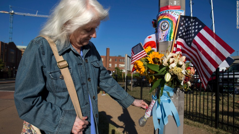 "A woman who said she works at the Washington Navy Yard looks at a memorial to the shooting victims on Wednesday, September 18. Authorities said 12 people -- plus the gunman -- were killed in the shooting on Monday, September 16. <a href=""http://www.cnn.com/2013/09/16/us/gallery/navy-yard-shooting/index.html"">View photos from the scene of the rampage.</a>"
