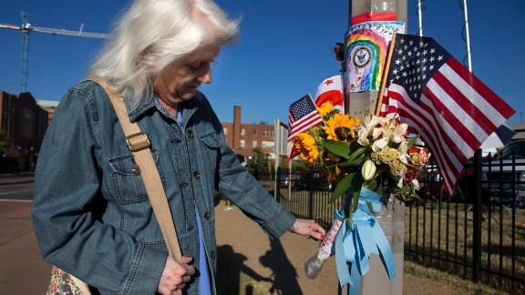 A woman who said she works at the Washington Navy Yard looks at a memorial to the shooting victims on Wednesday, September 18. Authorities said 12 people -- plus the gunman -- were killed in the shooting on Monday, September 16. View photos from the scene of the rampage.