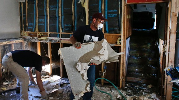 David Soleta, right, and family friend John Rice remove destroyed and contaminated walls on September 18 from Soleta's father-in-law's home, which was heavily damaged by floodwaters that swept through Longmont.